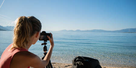 View from behind of a young female photographer setting up camera on tripod by the sea. Archivio Fotografico