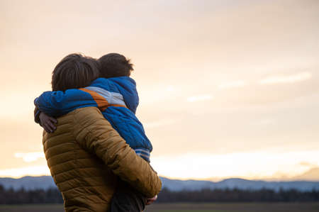 Beautiful moment between a father and son hugging each other while standing under beautiful evening sky enjoying nature and sunset.
