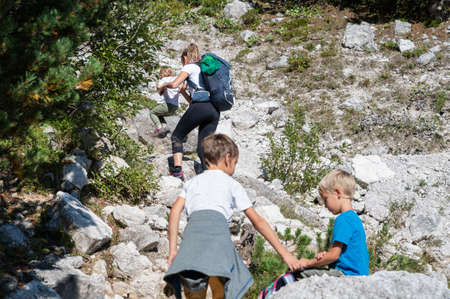 Young mother hiking in mountains with her three children. Archivio Fotografico