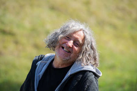 Portrait of a cheerful senior homeless man with a bright smile.