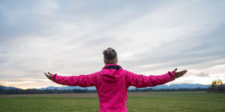 View from behind of a young woman in pink jacket standing with her arms wide open under an evening sky.