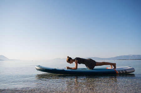 Fit young woman making a plank strength exercise on a sup board floating on calm morning sea water.