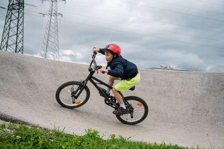Young boy riding his bmx bike on a pumptrack.