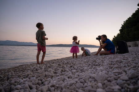 Young mother photographing her three children playing on pebble beach in a beautiful summer evening.