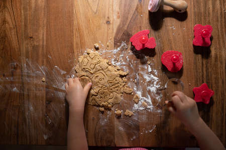 Top view of a child making homemade vegan cookies with a dough and cookie cutters of various shapes. Archivio Fotografico