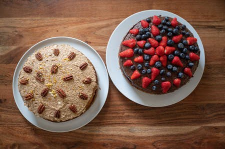 Top view of two delicious vegan cakes, one chocolate decorated with berries and the other carrot cake decorated with pecans.