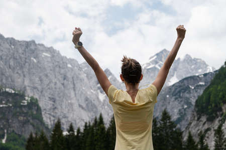 View from behind of a young woman standing under beautiful rocky mountains with her arms raised high.
