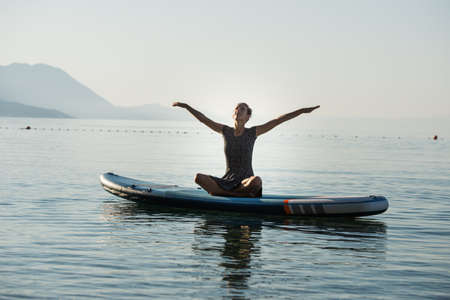 Young woman celebrating life practicing yoga on sup board floating on calm morning sea water.