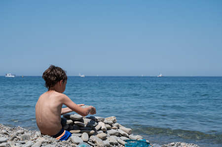 Child playing with rock on the beach on a beautiful sunny day. Archivio Fotografico