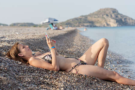 Young woman in a bikini lying on a beautiful pebble beach with her legs cooling in the sea while browsing on her mobile phone.