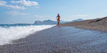 Young woman in pink bikini running on a beautiful pebble beach along the sea.