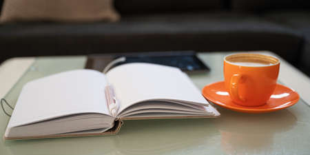 Open notepad with pen in the middle, cup of coffee and digital tablet lying on a coffe table in the living room.