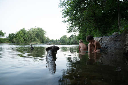 Two young boys playing in a beautiful peaceful Kolpa river sided with beautiful green trees.