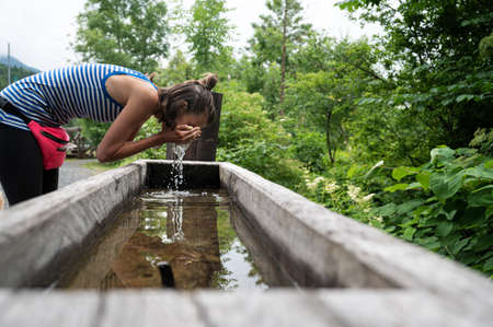 Young woman washing her face in a wooden trough placed in green nature. Archivio Fotografico