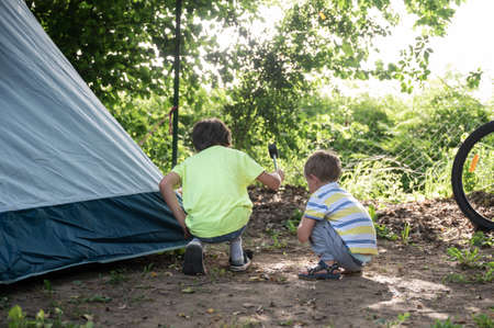 Two toddler boys hammering a spike for camping tent in the ground. Archivio Fotografico