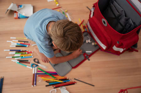 Back to school conceptual image - little boy sitting on the floor next to a school bag arranging his pencil case with color pencils.