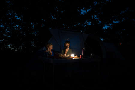 Two brothers sitting by their tent in a camping place eating dinner by a dimmed light. Archivio Fotografico