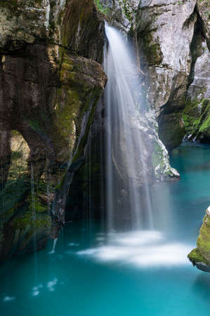 Beautiful blue river of Soca, Slovenia, with a blurred small waterfall flowing between rocky gorge.