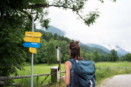 Young female hiker with a backpack looking at a signpost deciding which way to go.
