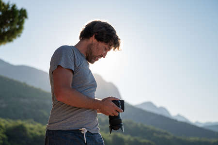 Young male photographer checking the settings on display of his dslr camera, standing outside on a beautiful summer morning.
