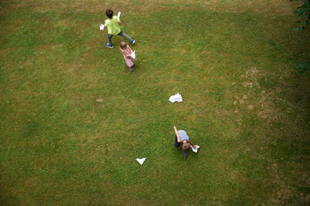 Top view of three kids playing with paper made origami planes on a green grass.