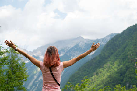 View from behind of a young woman standing outside in green nature looking at mountains with her arms spread widely.