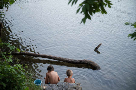 High angle view of two boys, brothers, sitting in a beautiful river of Kolpa observing the water life and playing.