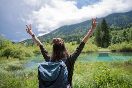 Happy young woman standing by the beautiful green water of Zelenci with her backpack and her arms raised high in triumph.