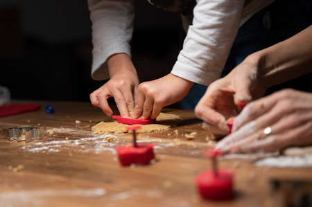 Low angle closeup view of a child making homemade cookies with her mother on a wooden dining table. 免版税图像