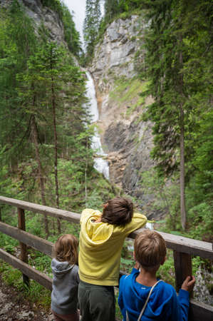 Three children leaning on wooden fence looking at a beautiful Martuljek waterfall falling down the rocks in green summer nature.