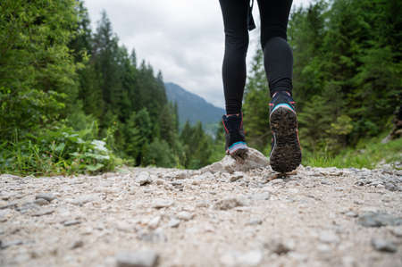 Low angle view of a woman in hiking boots walking on a gravel path in beautiful green nature.