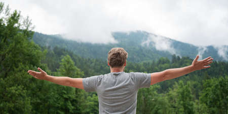 View from behind of a young man standing in beautiful green nature with his arms spread widely, enjoying life and abundance.