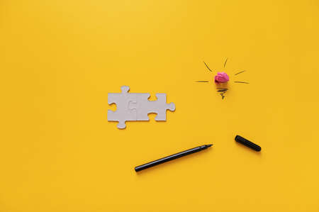 Brainstorming and idea conceptual image - light bulb, pen and two blank matching puzzle pieces on yellow background. 免版税图像