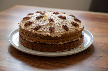 Beautiful vegan carrot cake with icing and decorated wit pecan nuts on a wooden table.
