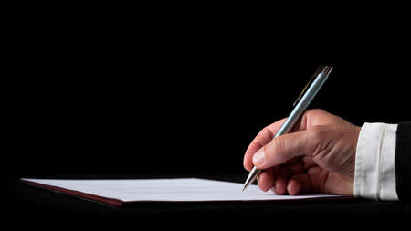 Hand of a businessman signing a document or contract on black desk over black background.