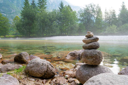 Tower of rocks by the beautiful calm river of Soca with green trees in background.