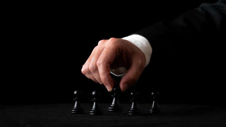 Hand of a businessman arranging chess figures in a conceptual image of leadership and power. Over black background.