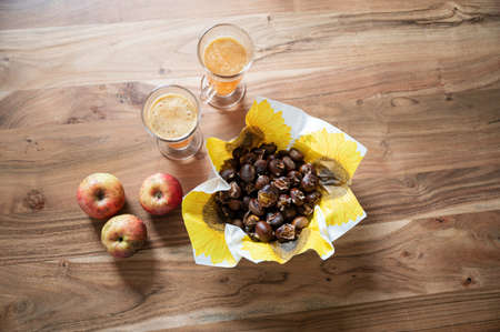 Top view of baked chestnuts in a basket next to fresh apples and hot apple cider on wooden desk.
