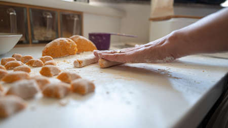Low angle closeup view of female hands rolling homemade pasta dough to make delicious vegan gnocchi.