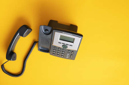 Top view of black landline telephone with handset off the hook. Over yellow background.