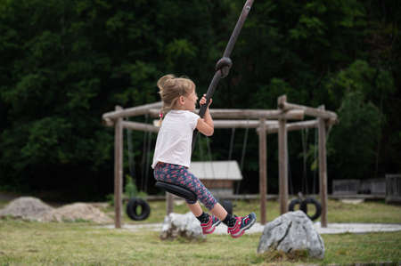 Cheerful toddler girl riding on a zipline like swing outside on a playgorund. 免版税图像