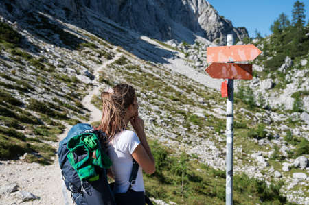 Young female hiker with a backpack contemplating standing by a signpost in the middle of mountain hiking trail.