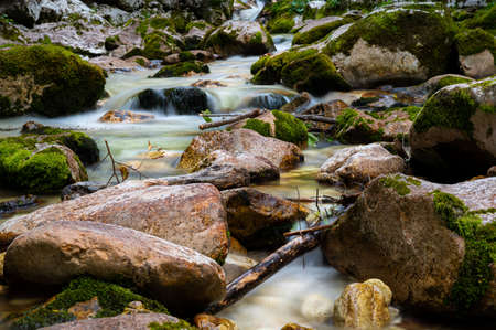 Blurred image of a beautiful stream of water flowing through mossy rocks.