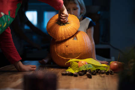 Toddler children looking at a halloween pumpkin they just carved. 免版税图像