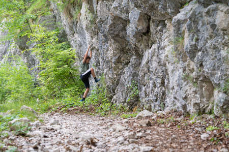 Young boy trying to climb up the rocks outside in a beautiful nature. 免版税图像