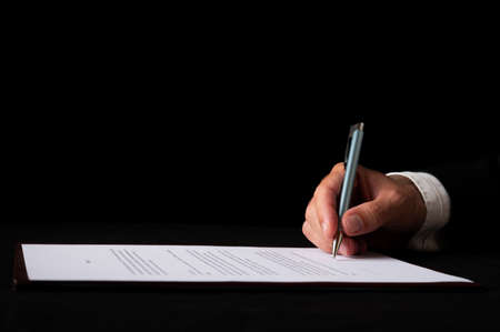 closeup view of a hand of a businessman signing a document or contract. Over black background. 免版税图像