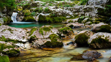 Blurred image of a beautiful stream of green water flowing through mossy rocks.