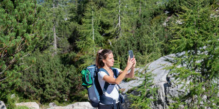 Young female hiker with a backpack taking a photo with her mobile phone of the beautiful nature around her.