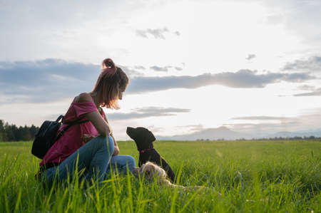 Young woman outside in a beautiful green meadow  kneeling down to her two dogs looking at her with attention and trust.
