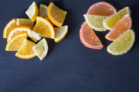 Colorful sugary marmalade. Lemon and orange slices covered with sugar. Fruit jelly candies. Closeup. Top view on slate background Stock Photo
